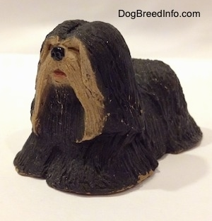 The front left side of a figurine of a black with tan Tibetan Terrier standing. The figurine has a black circle for a nose.