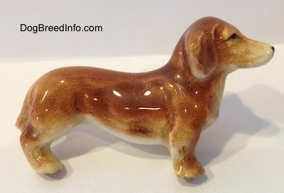 The right side of a tan ceramic Dachshund dog figurine. The figurine has a broken leg. The ear of the figurine is attached to its body and it is hard to differentiate.