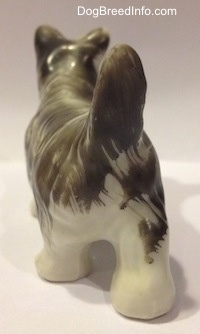 The back of a porcelain grey and white Miniature Schnauzer figurine. The figurine has a long tail that is arched in the air.