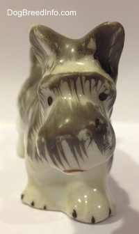 A porcelain figurine of a grey and white Miniature Schnauzer. The figurine has black circles for eyes