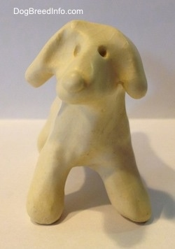 A ceramic white dog that has a holes for eyes.