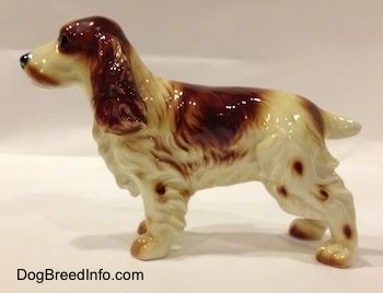 The left side of a red and white Welsh Springer Spaniel figurine. The figurine has spots up and down its legs.