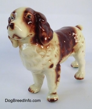 The front left side of a brown and white figurine of a Welsh Springer Spaniel. The figurine has black circles for eyes.