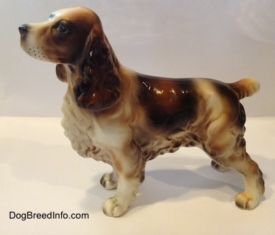 The left side of a porcelain white with brown and black Welsh Springer Spaniel standing figurine. The figurine has fine hair details along its body.
