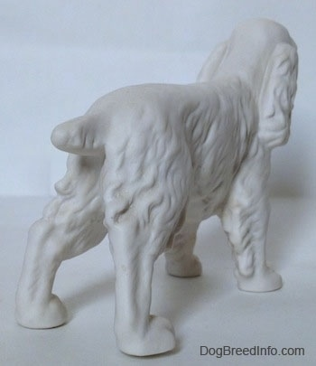 The back right side of a figurine of a white bisque unpainted Welsh Springer Spaniel figurine. The figurine has a short cropped tail.