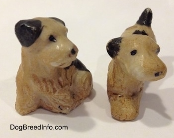 Two figurines of Welsh Terrier puppies. The figurines have black circles for eyes.