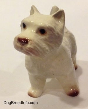 A white with tan figurine of a West Highland Terrier. The figurine has black circles for eyes.