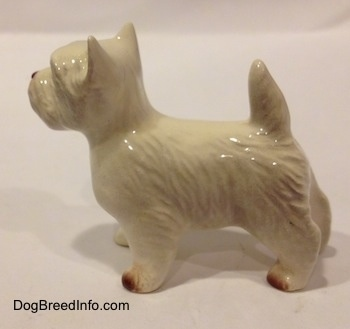 The left side of a white with tan figurine of a West Highland Terrier. The figurine is glossy.