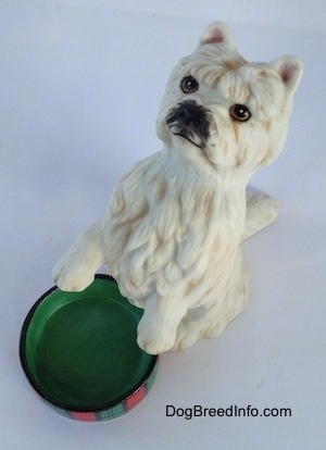 Top down view of a figurine of a West Highland White Terrier in a begging pose. The figurine has a black nose and black around it.