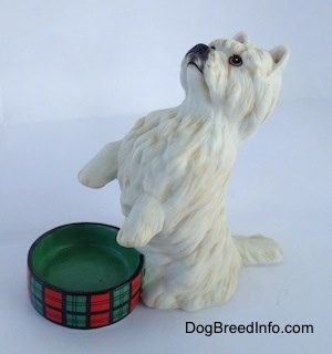 The front left side of a West Highland White Terrier figurine in a begging pose next to an empty dish. The figurine has short standing ears.
