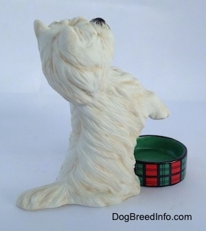 The right side of a West Highland White Terrier in a begging pose with an empty dish in front of it figurine. The figurine has a short tail.