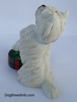 The back left side of a figurine of a West Highland White Terrier figurine in a begging pose with an empty dish. The figurine has fine hair details.
