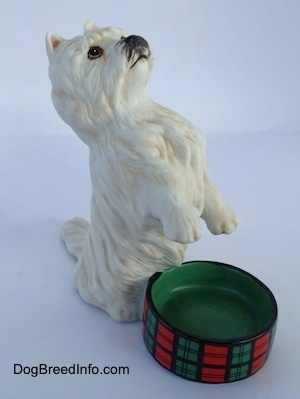 The front right side of a porcelain West Highland White Terrier in a begging pose next to an empty dish figurine. The figurine has fine hair details.