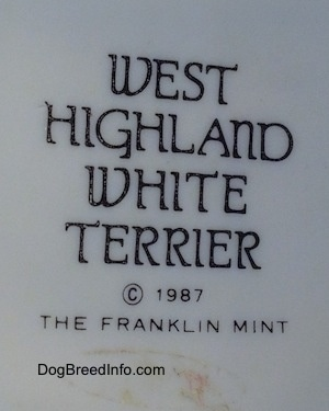The underside of a West Highland Terrier White figurine. The figurine has a black stamp that reads 'West Highland White Terrier ©1987 The Franklin Mint'.