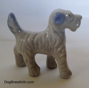 The right side of a figurine of a porcelain white with blue Wire Fox Terrier. The figurie has the word 'JAPAN' engraved on its side.