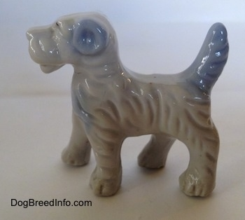 The right side of a porcelain figurine of a white with blue Wire Fox Terrier that has blue ears.