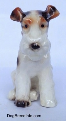 A white with black and brown figurine of a Wire Fox Terrier sitting. The figurine has medium length legs.