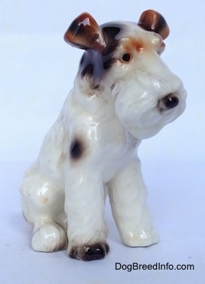 The front right side of a white with black and brown Wire Fox Terrier sitting figurine. The figurine has black circles for eyes.