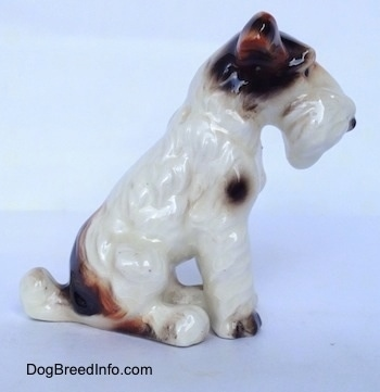 The right side of a white with black and brown Wire Fox Terrier figurine in a sitting pose. The figurine has fine hair details along its body.