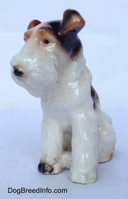 The front left side of a figurine of a white with black and brown sitting Wire Fox Terrier. The ears of the figurine are flopped over.