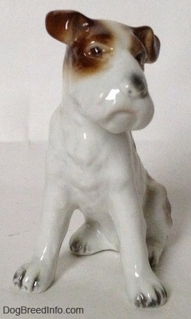 A figurine of a white with brown Wire Fox Terrier sitting figurine. The ears of the figurine are flopped over.