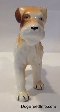 A standing figurine of a white and tan Wire Fox Terrier. The figurine has small black circles for eyes.