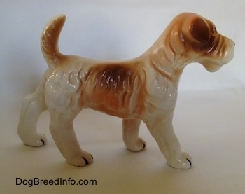 The right side of a white and tan figurine of a standing Wire Fox Terrier. The figurine has an arched up tan tail.