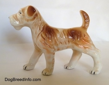 The left side of a white and tan Wire Fox Terrier figurine in a standing pose. The figurine has tan flopped over ears.