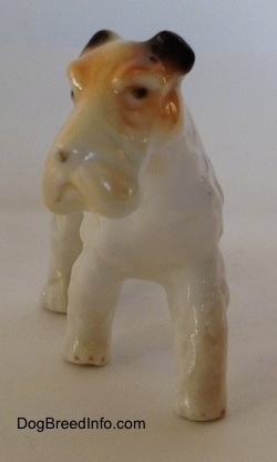 A figurine of a white with black and tan bone china Wire Fox Terrier. The figurine has small black circles for eyes.