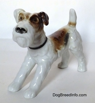 The front left side of a figurine of a white with black and brown Wire Fox Terrier. The figurine has black circles for eyes.
