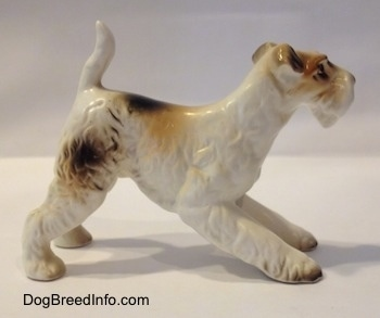 The right side of a figurine of a ceramic white with tan and black Wire Fox Terrier. The figurine has flopped over ears.