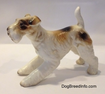 The left side of a ceramic white with tan and black figurine of a Wire Fox Terrier. The figurine has fine hair details along its body.