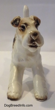 A ceramic white with tan and black Wire Fox Terrier figurine. The figurines face lacks detail.
