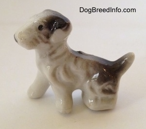 The left side of a white with black bone china figurine of a Wire Fox Terrier.