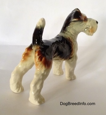 The back right side of a black and white with brown Wire Fox Terrier figurine. The figurine has a long tail that is in the air.
