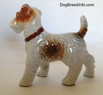 The left side of a porcelain white with tan standing Wire Fox Terrier figurine. The figurine has fine hair details along its body and a big brown spot on its side.