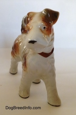 A white with tan figurine of a Wire Fox Terrier standing. The figurine has small black dots for eyes.