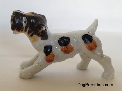 The left side of a white with black and brown bone china Wire Fox Terrier in a play bow pose figurine. The figurine has black and brown spots along its body.