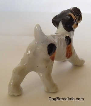 The back right side of a bone china white with black and brown Wire Fox Terrier figurine in a play bow pose. The figurine has a short tail that is arched in the air.