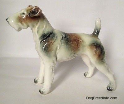 The left side of a white with brown and black Wire Fox Terrier figurine. The figurine has long legs with black tipped nails.