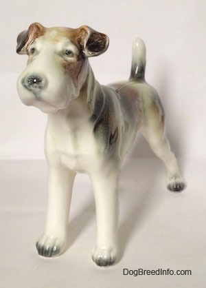 The front left side of a white with brown and black figurine of a Wire Fox Terrier. The figurine has small detailed eyes.