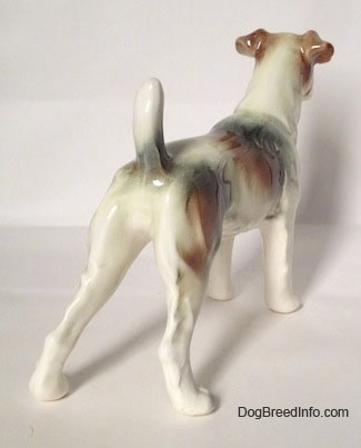 The back right side of a figurine of a white with brown and black Wire Fox Terrier. The figurine is glossy.
