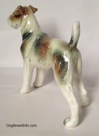 The back left side of a white with brown and black Wire Fox Terrier figurine. The figurine has brown and black patches along tis body.