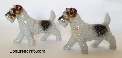 The left side of two figurines of white with black and brown Wire Fox Terriers. The figurines have brown ears.