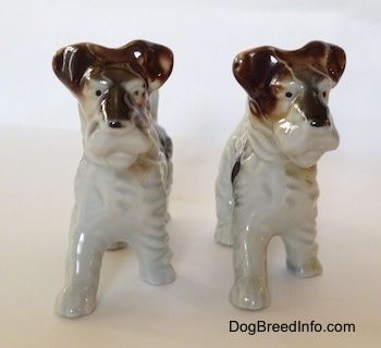 Two porcelain figurines of white with black and brown Wire Fox Terriers. They both have black dots for eyes.