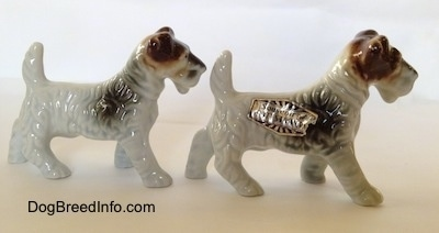 The right side of two white with black and brown Wire Fox Terrier figurines. The figurines have small legs.