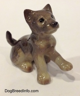 The front right side of a figurine of a Wolf cub sitting. The figurine is glossy.