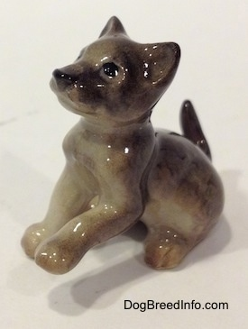 The left side of a gray figurine of a Wolf cub sitting. The figurines left paw is in the air.