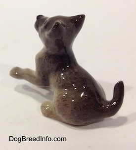 The back left side of a figurine of a Wolf cub sitting. The tail of the figurine is arched in the air.