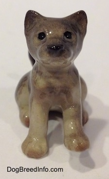 A figurine of a seated gray Wolf cub. The figurine has black circles for eyes.